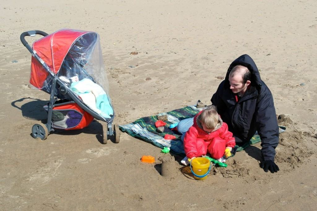 On the very windy beach - Georgie in her snowsuit and Lydia sheltered in the Graco Evo Mini by the cover.