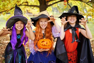 Halloween offspring: three children in stage costumes imitating Halloween children