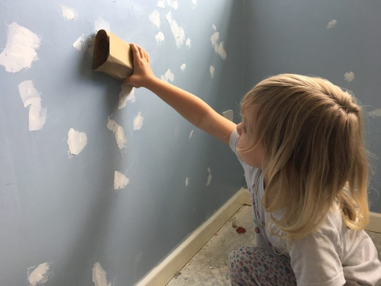 Lydia sanding the wall